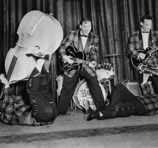 Bill Haley & His Comets at a Rehearsal... Bill Haley & His Comets rehearse at the Dominion Theatre in London, where they will open their British tour. The Comets include accordion player Johnnie Grande, bassist Al Rex, and saxophonist Ruddy Pompilli. February 6, 1957 London, England,